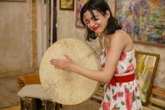 Una bruna attraente sta giocando un tamburino Immagine Stock
