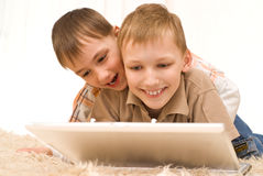 Una bugia dei due piccoli fratelli con il computer portatile Fotografie Stock