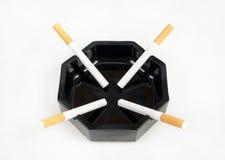 Una bugia delle quattro sigarette in un portacenere Immagini Stock Libere da Diritti