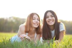 Una bugia di due giovani donne sull'erba Fotografia Stock