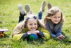 Una bugia di due ragazze su erba fotografie stock libere da diritti
