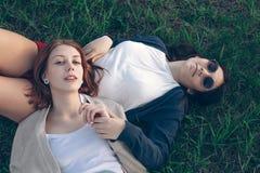 Una bugia di due ragazze su erba Fotografia Stock