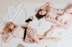 Una bugia di due ragazze sul pavimento fra gli accessori Immagini Stock