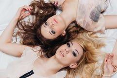 Una bugia di due ragazze sul pavimento fra gli accessori Immagini Stock Libere da Diritti