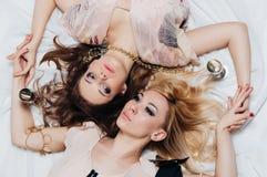 Una bugia di due ragazze sul pavimento fra gli accessori Immagine Stock