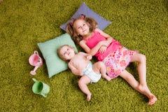 Una bugia di due sorelle su tappeto Fotografia Stock