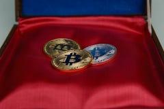 Una bugia di tre bitcoins sul fondo rosso del cofanetto immagine stock