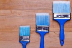Una bugia di tre spazzole su una scala Vista superiore di un fondo di legno immagine stock libera da diritti