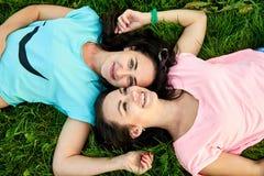 Una bugia felice di due ragazze sull'erba fotografia stock libera da diritti