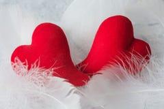 Una bugia rossa di due cuori su lanugine bianca fotografia stock