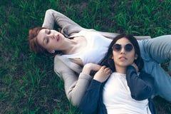 Una bugia sveglia di due ragazze sull'erba Immagine Stock