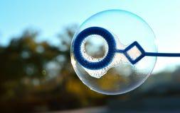 Una burbuja de jabón se infla contra el fondo del paisaje del otoño y del cielo azul Imágenes de archivo libres de regalías