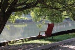 Una butaca roja vieja en el lago en el parque, bajo ramas de un árbol Foto de archivo