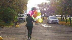 Una cámara lenta de una mujer que camina abajo de la calle con los globos coloridos metrajes
