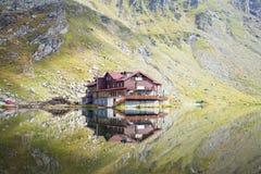 Una cabaña con la reflexión en el lago de la montaña Fotos de archivo libres de regalías