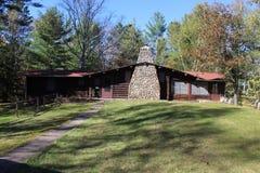 Una cabaña de madera con una chimenea de piedra de campo Imagenes de archivo