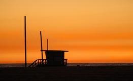 Una cabaña del salvavidas en una playa contra una puesta del sol de oro Imagen de archivo libre de regalías