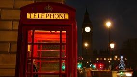 Una cabina de teléfono roja icónica en la casa de Front Of Big Ben And del parlamento en Londres, Reino Unido en la noche metrajes
