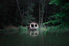 Una cabina en el bosque por el lago Imágenes de archivo libres de regalías