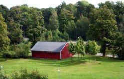 Una cabina rossa fra il legno Immagine Stock