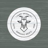 Una cabra se dibuja en un estilo linear para un logotipo de la granja en un fondo de la textura de madera del vector stock de ilustración