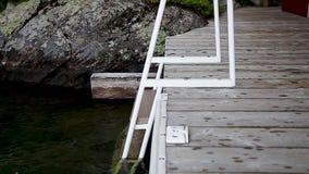 Una cacerola de un carril de la natación en un muelle al lado de un lago almacen de video