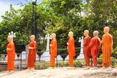 Una cadena de estatuas de monjes budistas en tonos anaranjados en un templo budista en Sri Lanka Imagenes de archivo