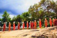 Una cadena de estatuas de monjes budistas en tonos anaranjados en un templo budista en Sri Lanka Fotografía de archivo libre de regalías