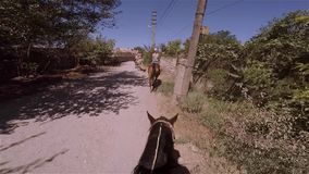 Una cadena de jinetes monta a caballo uno tras otro a lo largo de una carretera nacional a través del pueblo almacen de video