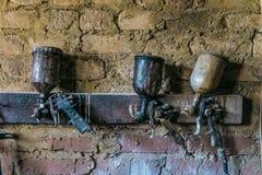 Una caduta pneumatica di tre pistole a spruzzo sulla parete Fotografia Stock Libera da Diritti