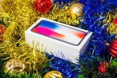 Una caja con un smartphone en una malla del árbol de navidad Fotos de archivo
