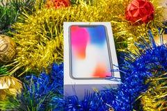 Una caja con un smartphone en una malla del árbol de navidad Imagenes de archivo