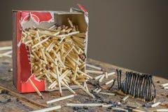 Una caja de cerillos y partidos quemados Fotografía de archivo libre de regalías