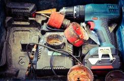 Una caja de herramientas con los taladros, destornillador y los engranajes fotografía de archivo