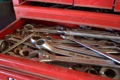 Una caja de herramientas roja abierta que contiene las llaves inglesas, los desplazadores y los zócalos Fotos de archivo libres de regalías