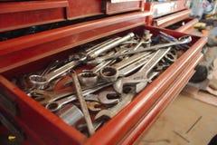 Una caja de herramientas roja del cajón abierto que muestra desplazadores, las llaves inglesas y los zócalos Foto de archivo libre de regalías