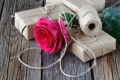 Una caja de la rosa y de regalo del rojo con la cinta en la tabla de madera rústica con el espacio de la copia Foto de archivo