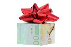 Una caja de regalo envuelta con el dinero euro adornado con la cinta roja del regalo Fotos de archivo libres de regalías