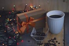 Una caja de regalo marrón con un arco anaranjado y taza azul en el tablenn Imagen de archivo