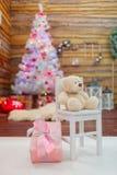 Una caja de regalo y un oso de peluche están en el fondo de un árbol de navidad decorativo dentro Imagenes de archivo
