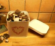 Una caja metálica sobrellenada con el caramelo hecho en casa de la Navidad fotografía de archivo