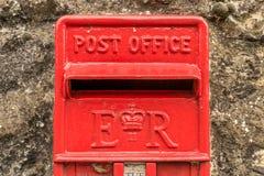 Una caja roja británica de los posts situada en una pared fotos de archivo libres de regalías