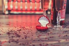 Una caja roja con un anillo, propuesta de matrimonio, día de tarjetas del día de San Valentín, vino, atmósfera romántica Foto de archivo libre de regalías