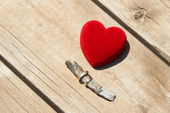 Una caja roja del terciopelo con un par de anillos de bodas del oro Fotografía de archivo