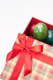 Una caja roja hermosa con un arco rojo y los huevos de Pascua Fotos de archivo libres de regalías