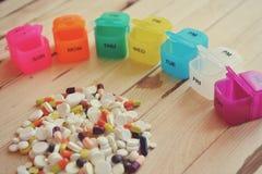 Una caja semanal plástica de la píldora Caja diaria de la píldora con las medicaciones y los suplementos alimenticios Imagen de archivo libre de regalías
