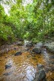 Una cala grande con muchas piedras y rocas y agua clara Fotos de archivo