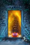 Una calabaza anaranjada divertida con brillar intensamente observa delante de puerta del ` s del infierno fotografía de archivo libre de regalías