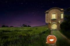 Una calabaza en el camino del viejo medievalhouse del vintage al lado del campo de trigo con la luz caliente dentro en la noche Imagen de archivo libre de regalías