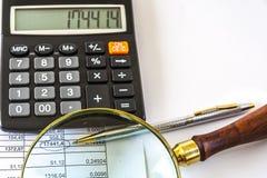 Una calculadora, documento de negocio de Pen And Magnifying Glass On imagen de archivo libre de regalías